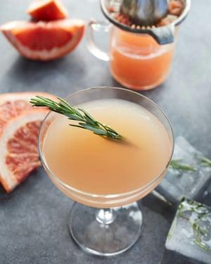 Margarita de naranja sanguina con romero y margarita de hielo derretido con naranja sanguina con una ramita de romero, rodajas de naranja, carámbanos derretidos y jugo de naranja recién exprimido sobre una superficie de concreto