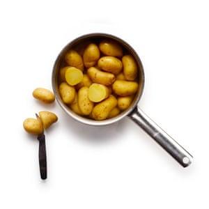 Hervir las papas cerosas hasta que estén tiernas pero no completamente cocidas, luego escurrir y secar al vapor.