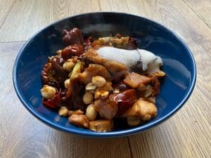 El pollo kung pao de Andrew Wong comienza con caldo de kung pao, aromatizado con granos de pimienta de Sichuan, pimientos secos, jengibre y ajo.