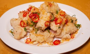 Calamares a la sal y pimienta con anillos de pimiento rojo en un plato redondo blanco