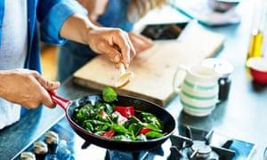 Primer plano de un hombre que sostiene una sartén con verduras frescas y una cuchara de madera