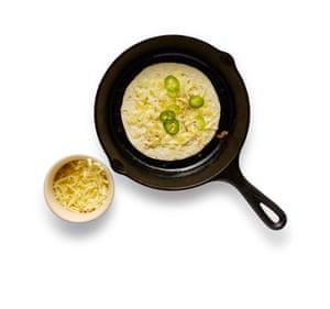Coloque una tortilla en una sartén caliente y decore con queso. Cuando comience a derretirse, agregue orégano y chile y observe.