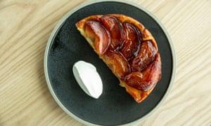 Un croissant de tarta de manzana y una gota de crema en un plato redondo y oscuro