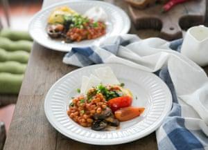 Desayuno con frijoles Desayuno con frijoles y tomates de pie sobre un piso de madera. Tiro horizontal en interiores.