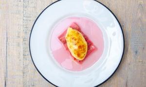 Un plato blanco redondo con un trozo oblongo de ruibarbo y un óvalo de crema en la parte superior, y jugo rosa en el plato