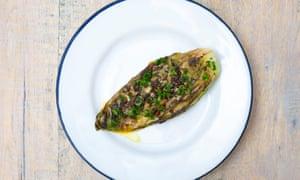 Un plato blanco redondo con un borde azul con un óvalo de repollo hispi en la parte superior y una salsa de mantequilla de hierbas en la parte superior