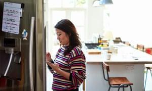Mediados de mujer adulta comprobando la comida en el refrigerador con tableta