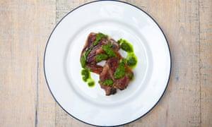Chuletas de cordero en un plato con grasa crujiente, carne rosa clara y salsa verde brillante punteada