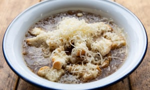 Un tazón blanco de sopa de cebolla francesa con queso rallado encima