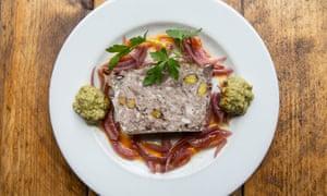 Un plato blanco redondo con una terrina oblonga en el medio y una dispersión de aros de cebolla roja marinados alrededor.