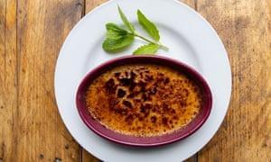 Un frasco redondo de terracota crème brûlée en un plato blanco redondo
