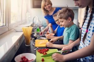 Madre y tres hijos preparan una comida