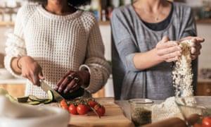 Las chicas irreconocibles cocinan en casa. Concepto de relación multirracial.