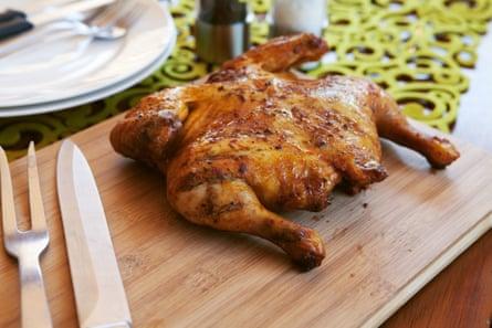Pollo entero cocinado con cubiertos y especias.