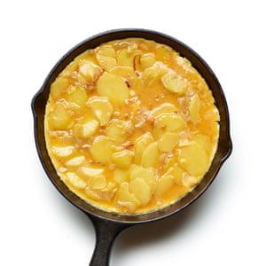 Tortilla española Felicity Cloake 05. Ponga la mezcla de huevo y papa en una sartén engrasada y fría hasta que la base esté crujiente.