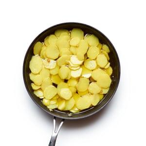 Tortilla española 03 de Felicity Cloake. Agregue las papas y cocine hasta que estén tiernas.