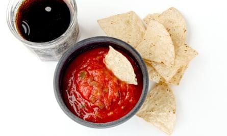 Primer plano de un tazón negro lleno de salsa con chips de tortilla junto a él con un tazón y un vaso de refresco en la parte superior izquierda del marco sobre un fondo blanco (de cerca arriba 39; un tazón negro lleno de salsa ingenio