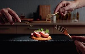 Tres manos sosteniendo tenedores para alcanzar el último sándwich