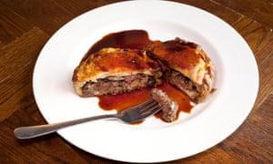 Pastel de bistec y riñón cortado abierto y con un tenedor sobre una placa blanca redonda