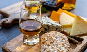 Maridaje de whisky y queso, degustación de vasos de whisky y plato con quesos en lonchas de cerca