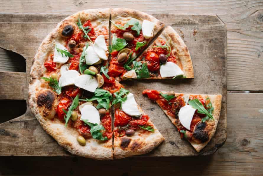 Pizza en rodajas sobre tabla de cortar