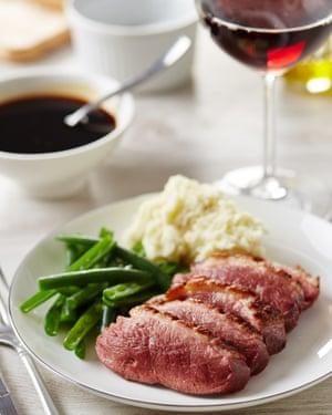 Pechuga de pato servida con puré de papas y judías verdes. Copa de vino tinto y salsa de fondo.