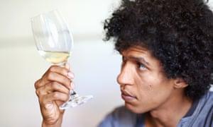 Hombre sujetando una copa de vino blanco mirando la calidad del vino en la copa