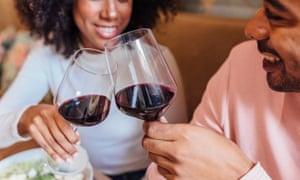 Feliz pareja romántica brindando con copas de vino en la cafetería
