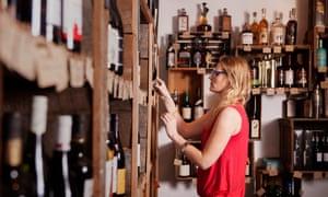 Vista lateral del propietario de la empresa examinando las botellas de vino en la tienda