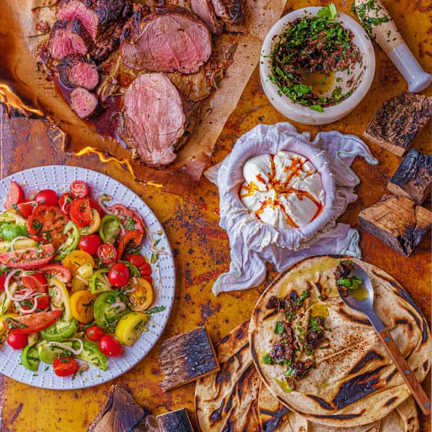 Pierna de cordero a la plancha, yogur átomo, tomates aliñados y panes planos con aceitunas negras y anchoas.