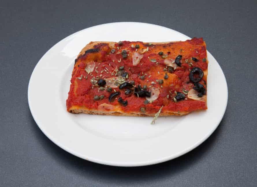 Pizza con tomates, aceitunas, ajo, datterini secados al sol, alcaparras, orégano en Mike's, Peckham, Londres.