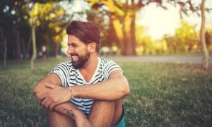 Retrato de hombre riendo en el parque, sentado en el césped en verano