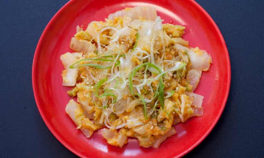 Un plato redondo rojo con kimchi dorado.