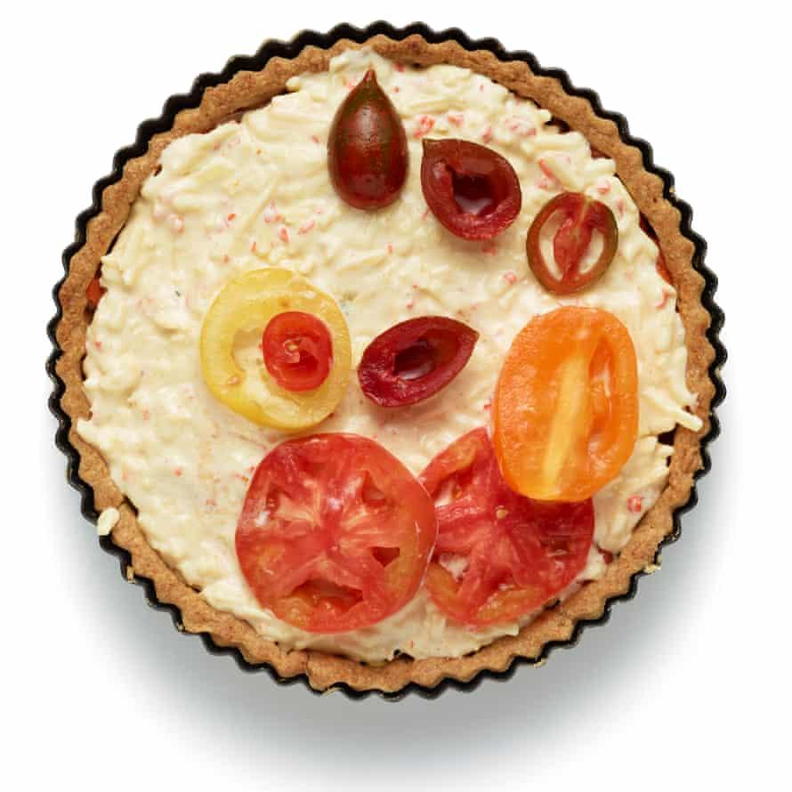 Para armar el pastel, espolvorea el resto del queso en la base, luego echa los tomates italianos horneados a la mezcla de cebolla y espárcelos encima. Unte la mezcla de mayonesa encima y luego termine con los tomates escurridos.